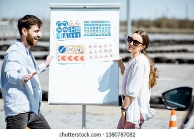 Male instructor showing traffic signs to a young female student standing on the training ground at the driver's school