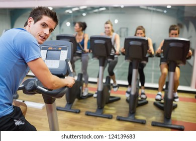 Male instructor at spinning class with four women in gym