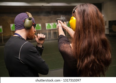 Male instructor teaches a girl to shoot a gun in the shooting range