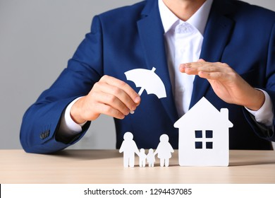 Male insurance agent covering paper family and home with umbrella cutout at table, closeup