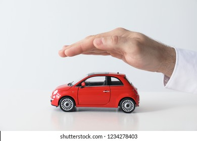 Male insurance agent covering toy car on white background, closeup