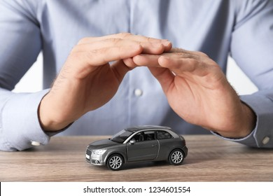 Male insurance agent covering toy car at table, closeup