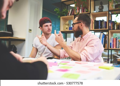 Male international student have training lesson about business startups and their successful concept, listening to coach detailed explanation sitting in modern university library with classmates