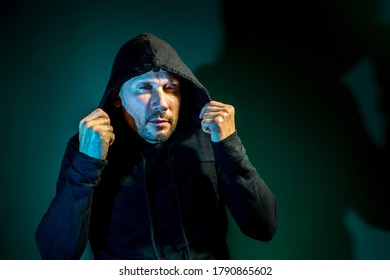A male intruder with a hood on his head poses on a dark green background
