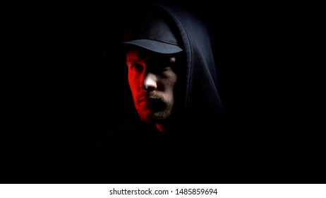 Male isolated on black background, red lights, escape from prison, conspiracy