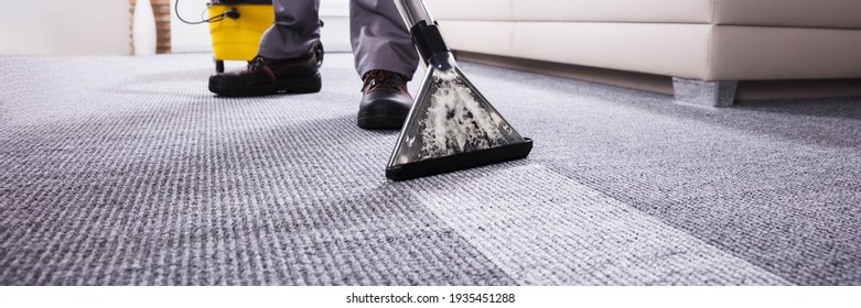 Male Janitor Cleaning Carpet With Vacuum Cleaning In The Living Room