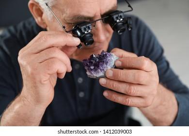 Male jeweler evaluating semi precious gemstone in workshop, closeup