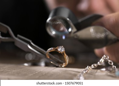 Male jeweler examining diamond ring in workshop, closeup view
