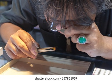 Male jeweler looking through a magnifier to check for flaws in a ruby. Experienced jeweller