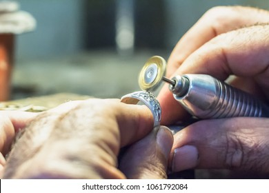 Male jeweler polishing a silver ring with a copper wire brush mounted on a flex shaft, motion effect.