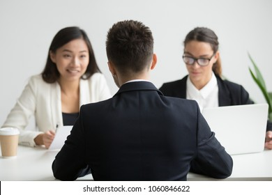 Male job applicant being interviewed by diverse HR representatives team discussing his work experience, sharing thoughts during recruitment process in company office. Concept of hiring, employment