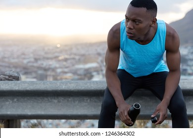 Male jogger rests after workout, holds bottle with refreshing drink, feels  tired, poses 03f6acb0b2