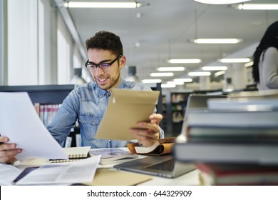Male journalist with eyeglasses checking written article on blank paper sitting at workplace in office interior, smiling intelligent student reading funny story in library during exam preparation