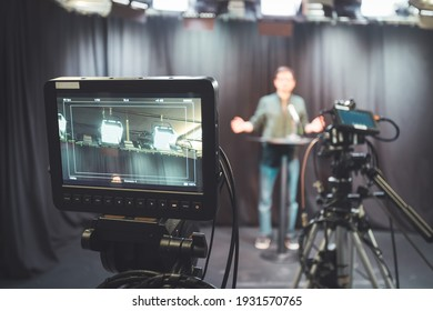 Male journalist in a television studio talks into a microphone, film cameras
