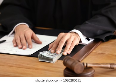 Male judge with bribe at table, closeup