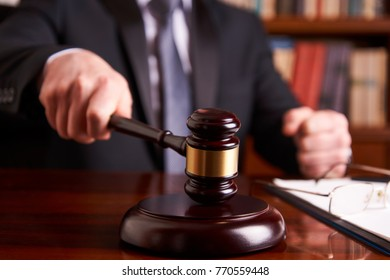 Male judge in a courtroom striking the gavel on wooden table. Legal law, advice and justice concept in lawyer office, close-up