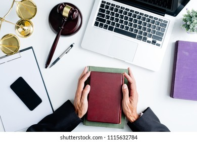 Male judge hand holding legal books on white wooden table in courtroom.justice and law concept.Top view.