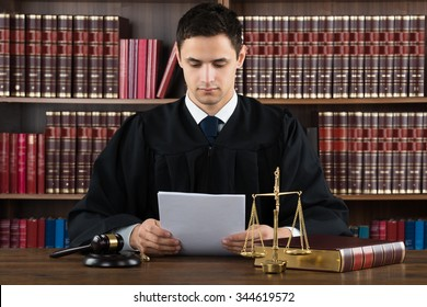 Male judge reading documents while sitting at desk in courtroom