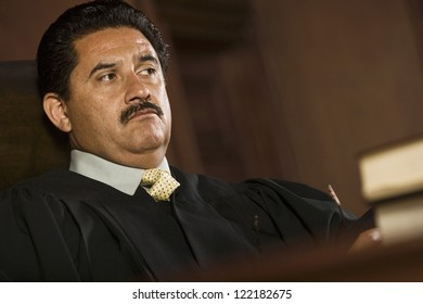 Male judge sitting with books in courtroom