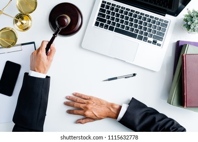 Male judge working with laptop computer, legal books and gavel on white wooden table in courtroom.justice and law concept.Top view.