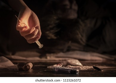 Male junkie hand holding drug injection syringe while lying near heroin powder, spoon and cigarette lighter for heroin cooking and money on dark floor. Hard drug addiction concept