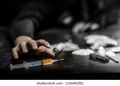 Male junkie hand trying to grab injection syringe of cooked heroine. Hard drug overdose and addiction concept