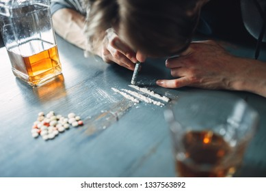 Male junkie sniffing a line of cocaine