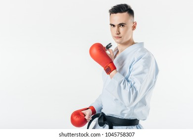 male karate fighter holding mouthguard and looking at camera isolated on white