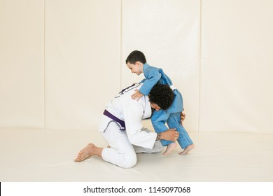 Male karate instructor training little child in dojo or jiu-jitsu at gym at tatami. Trainer teaches kid the basics of fighting for self-defense