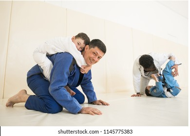 Male karate instructors training little children boys in dojo or jiu-jitsu at gym at tatami. Trainer teaches kid the basics of fighting for self-defense. Group of man and kids in training