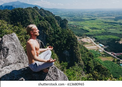 Male keeping balance in meditation. Shirtless man meditating in lotus pose on edge of high rock with picturesque tropical views on background.