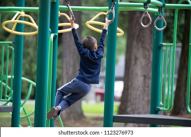 Male kid on the monkey-bars in the park on the children's playground.