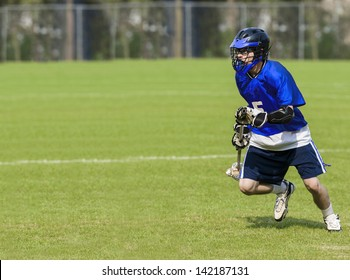 Male Lacrosse Player holding stick on a grass field with copy space
