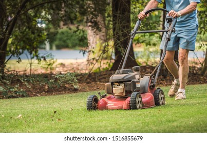 Male landscaper cutting backyard grass with gas powered lawn mower. Mowing residential lawn with walk behind push mower.