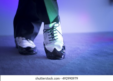 Male latin and salsa dancer in black and white jazz dancing shoes in light and dark on stage.