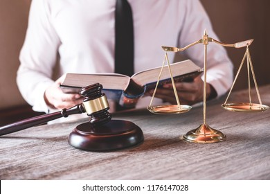 Male lawyer or judge working with Law books, gavel and balance, report the case on table in office, Law and justice concept.
