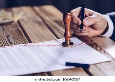 Male lawyer or notary signing document at his office. Law concept