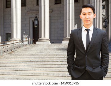 A male lawyer (or business person) stands in front of a courthouse or municipal building with his arms folded.