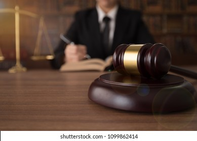Male lawyer reading legal books with gavel judge and scales of justice on desk in courtroom. concepts of law attorney ligislation.