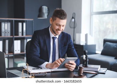 Male lawyer sitting at workplace in office