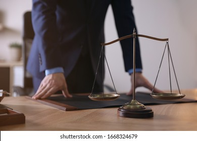 Male lawyer at table in office, focus on scales of justice