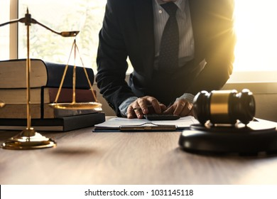 Male lawyer working with calculator and wooden gavel on tabel in courtroom. justice and law ,attorney, court judge, concept.