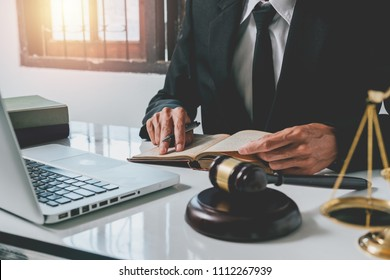 Male lawyer working with legal book and white desk table with laptop,gavel,scale.justice and law concept.