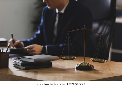 Male lawyer working at table in office, focus on scales of justice