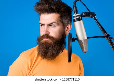 Male lead vocalist singing in recording studio. Vocalist singing in condenser microphone. Concert&music concept. Bearded man singing with microphone. Brutal bearded guy singer with microphone on stage