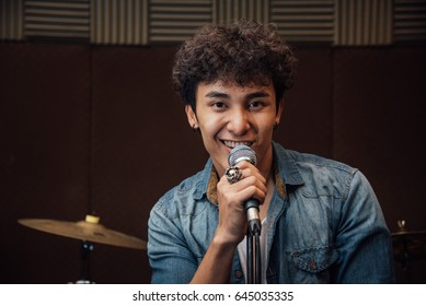 Male lead vocalist singing in studio with music instrument backg
