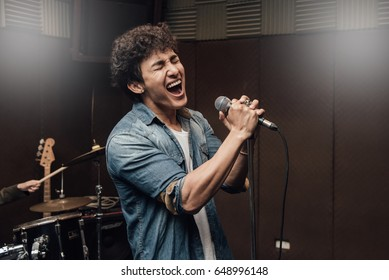 Male lead vocalist singing in studio with music instrument background.