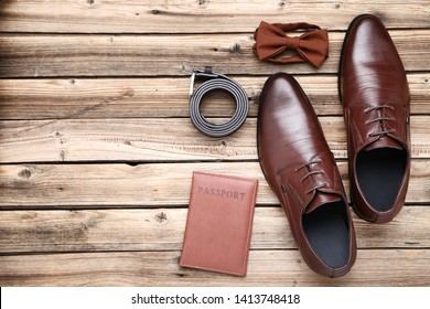 Male leather shoes with passport and accessories on brown wooden table