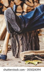 Male legs in jeans lying on the stump and log lying next to the ax