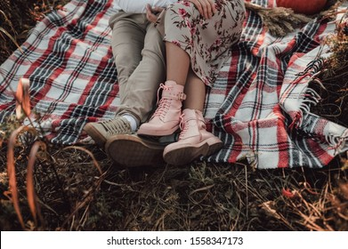 male legs in light shoes and female legs in pink boots sit on a plaid on an autumn picnic against a background of dry yellow grass